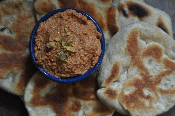 Muhamara (roasted red pepper dip) with feta and green olive stuffed flat bread
